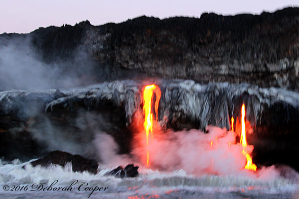 Lava cascades into the ocean sending plumes of steam into the air.